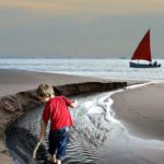 kid playing in the wet sand on beach with sailboat in background