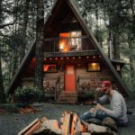 man building fire in front of cabin