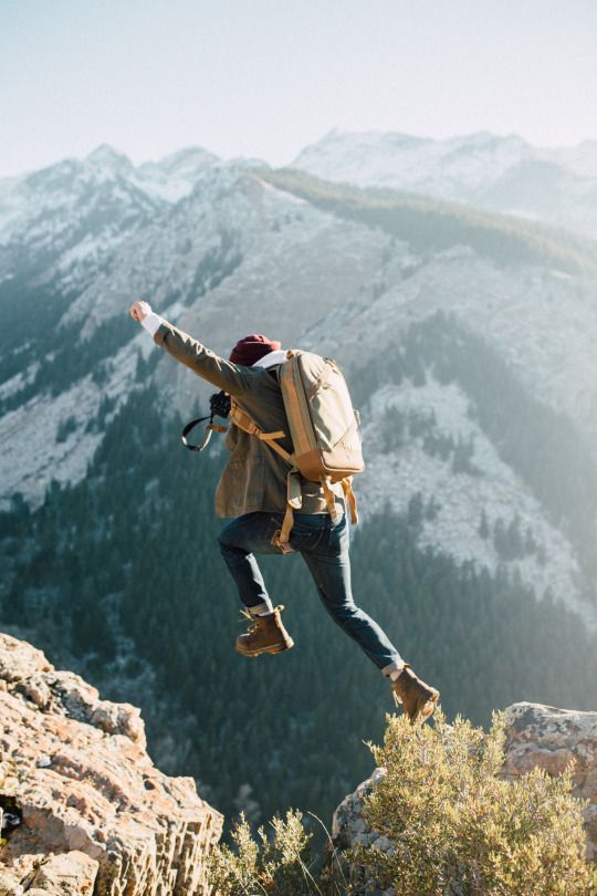 man jumping across mountain cliffs