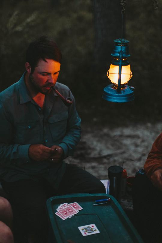 man smoking pipe while camping