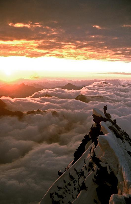 man on summit of mountain looking down on clouds
