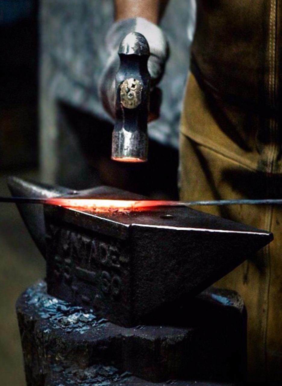 hammering hot metal on anvil