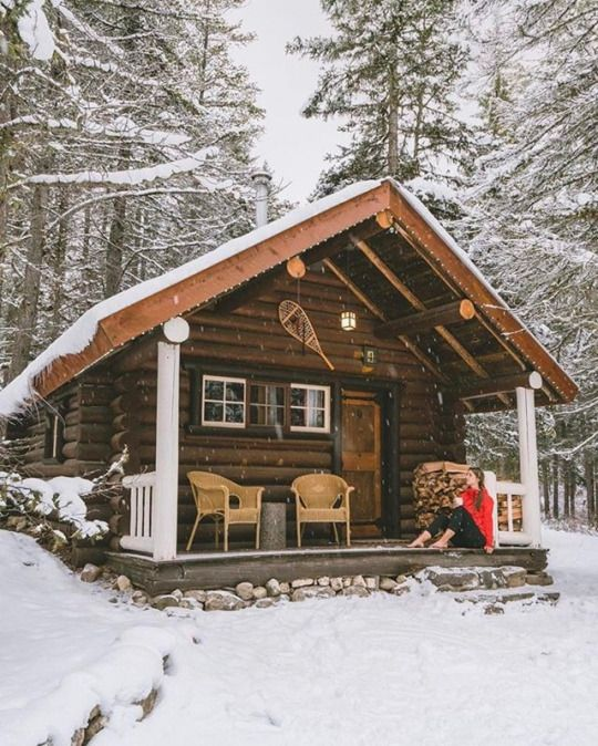 woman sitting on porch of cozy cabin