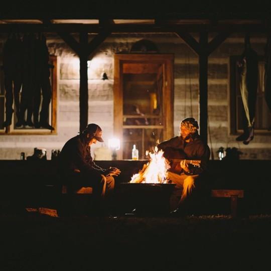 two male friends relaxing by fire