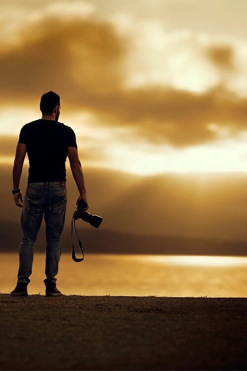 man holding camera watching sunset