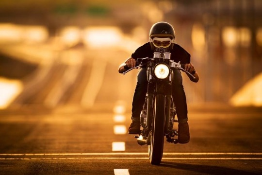 man riding cafe style motorcycle