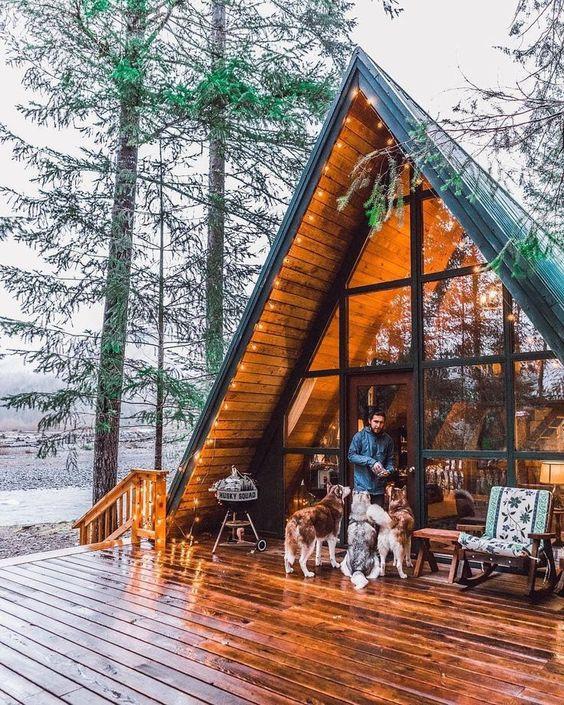 man feeding dogs outside cabin