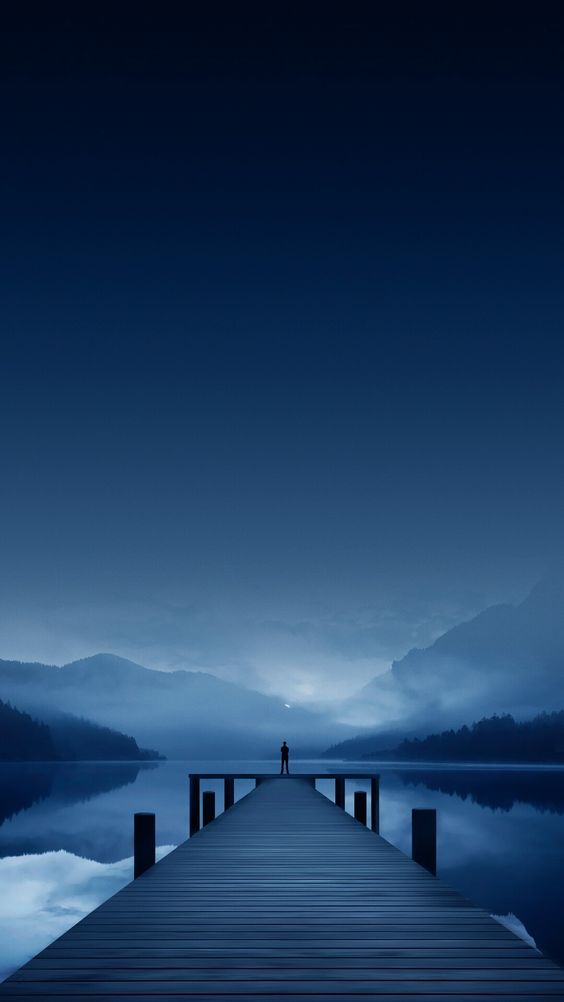 man standing at end of long dock