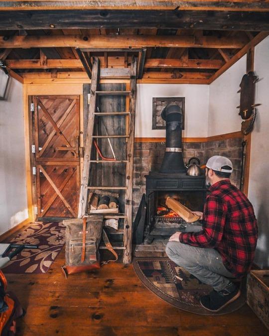 man tending to fire in cabin