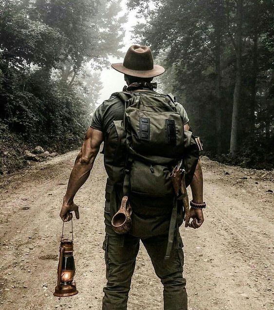 man walking on trail holding lantern