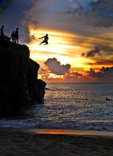 people jumping off cliff into ocean at sunset