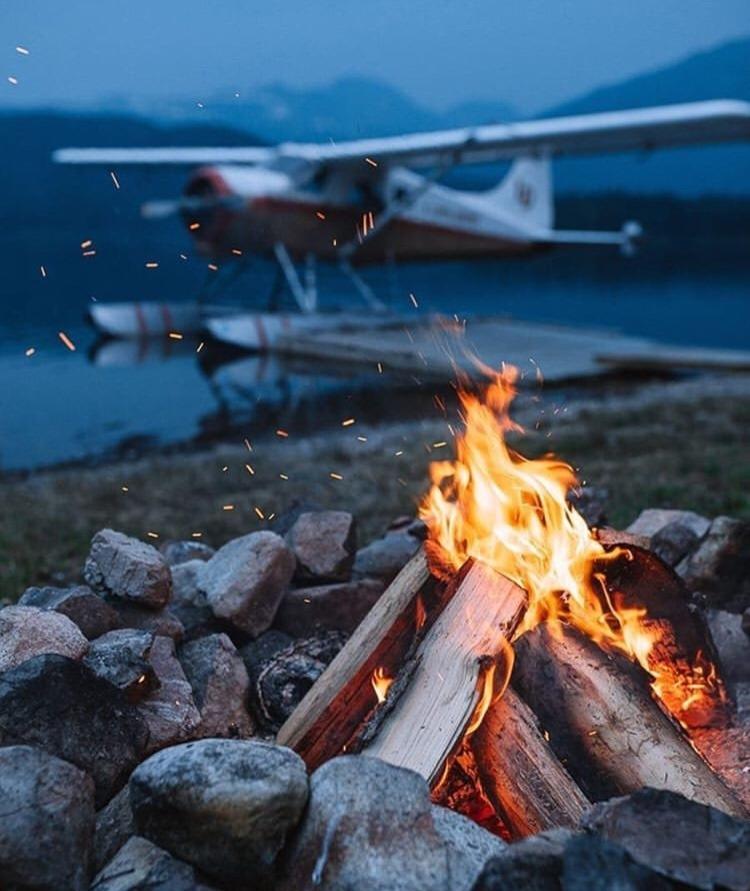 campfire near a lake with a plane