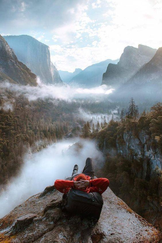 man lying down relaxing while enjoying view of yosemite valley