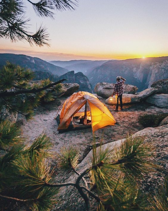 man standing near tent admiring mountain view