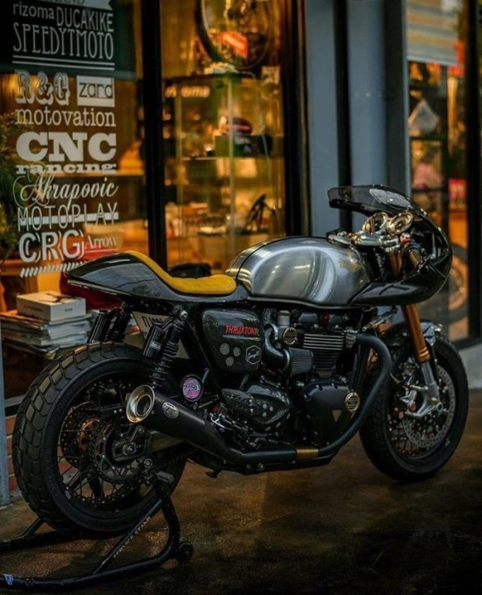 triumph motorcycle in front of shop