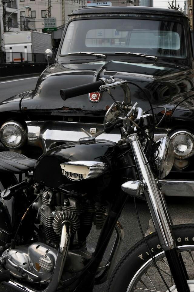 black classic triumph in front of black classic truck