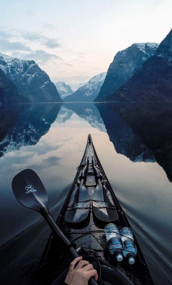 man canoeing through mountain lake