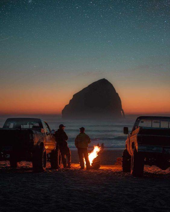 two men standing near campfire on oregon beach