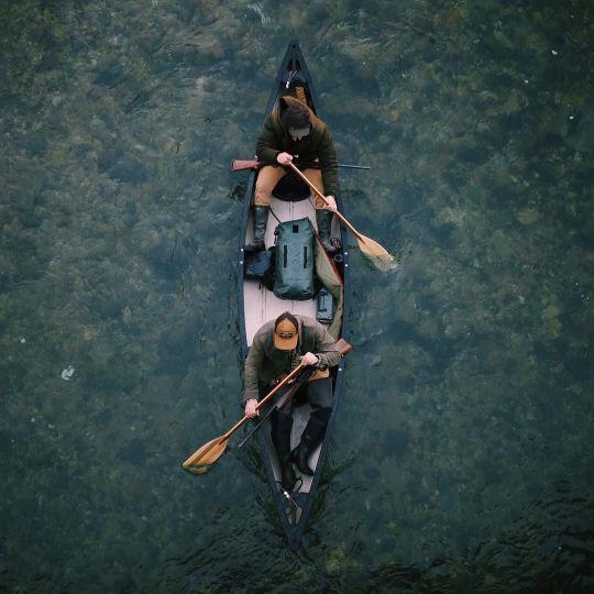 overhead shot of two men paddling boat on lake