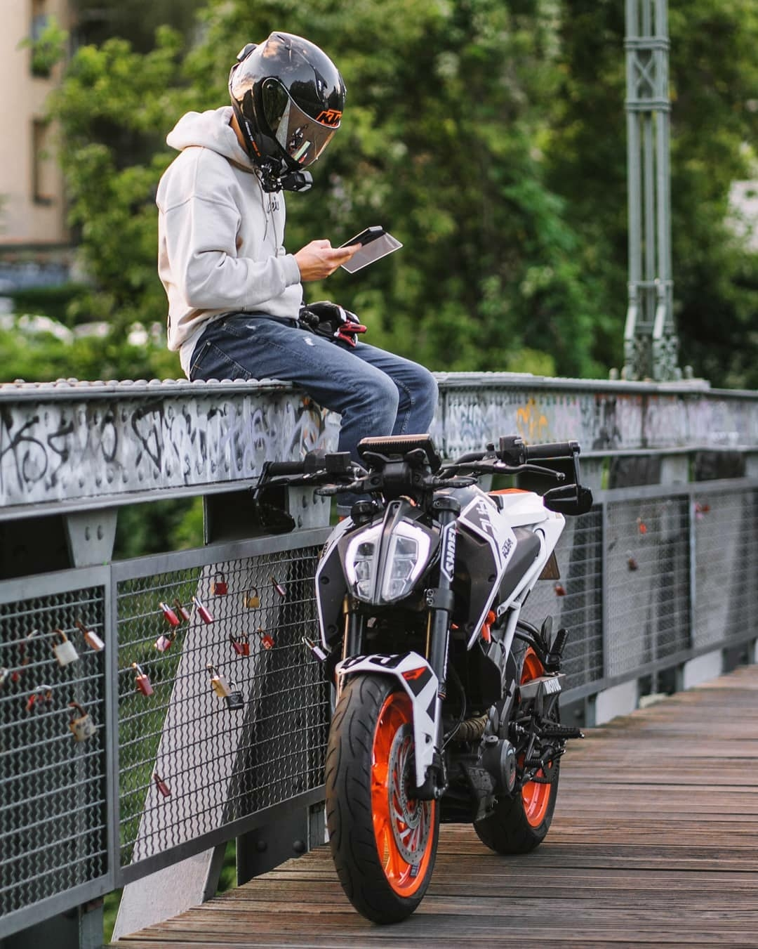 man checking his phone while sitting on bridge with helmet on and motorcycle near by