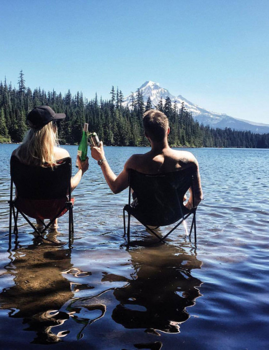 couple sitting on chairs in lake with mountain scene