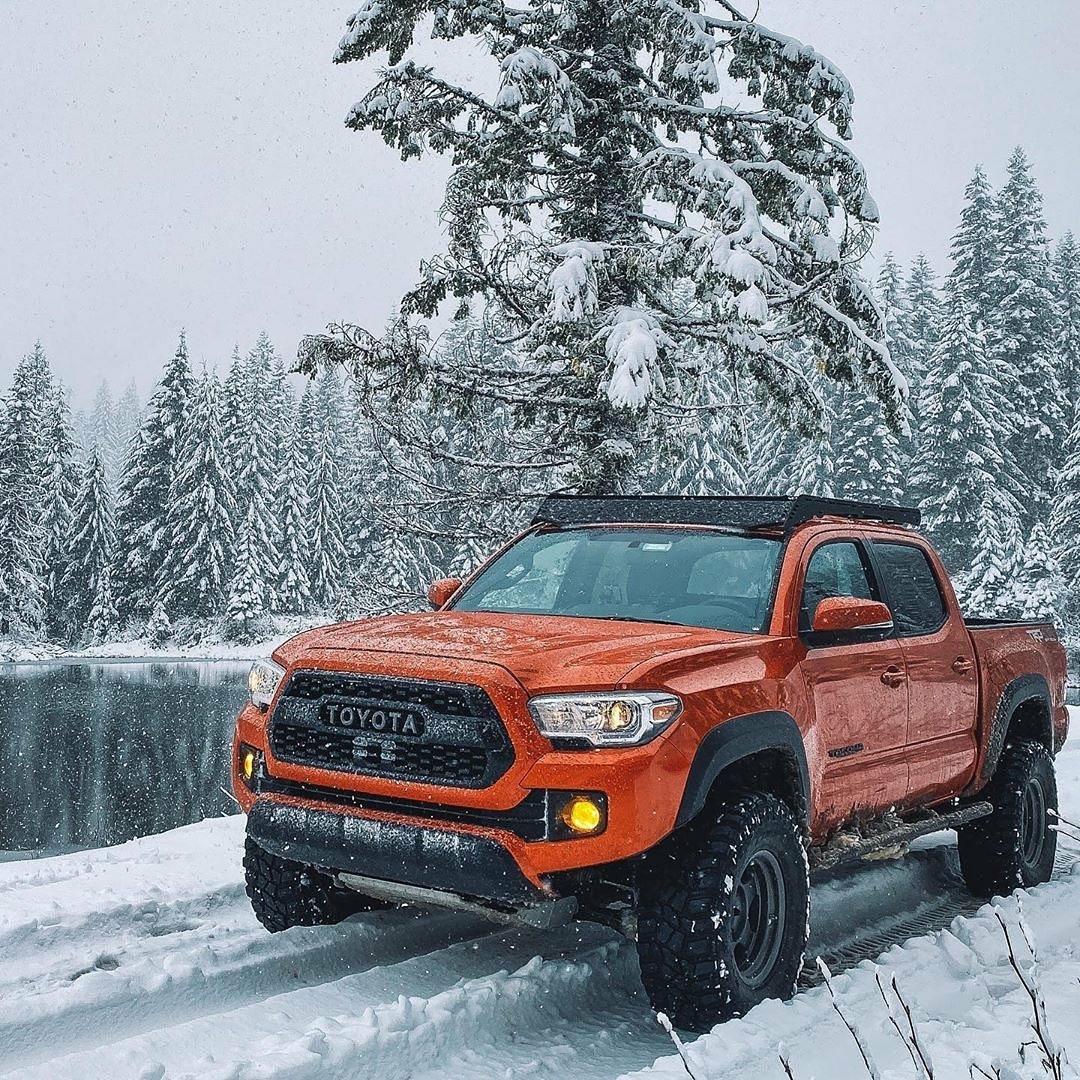 orange toyota pickup in the snow