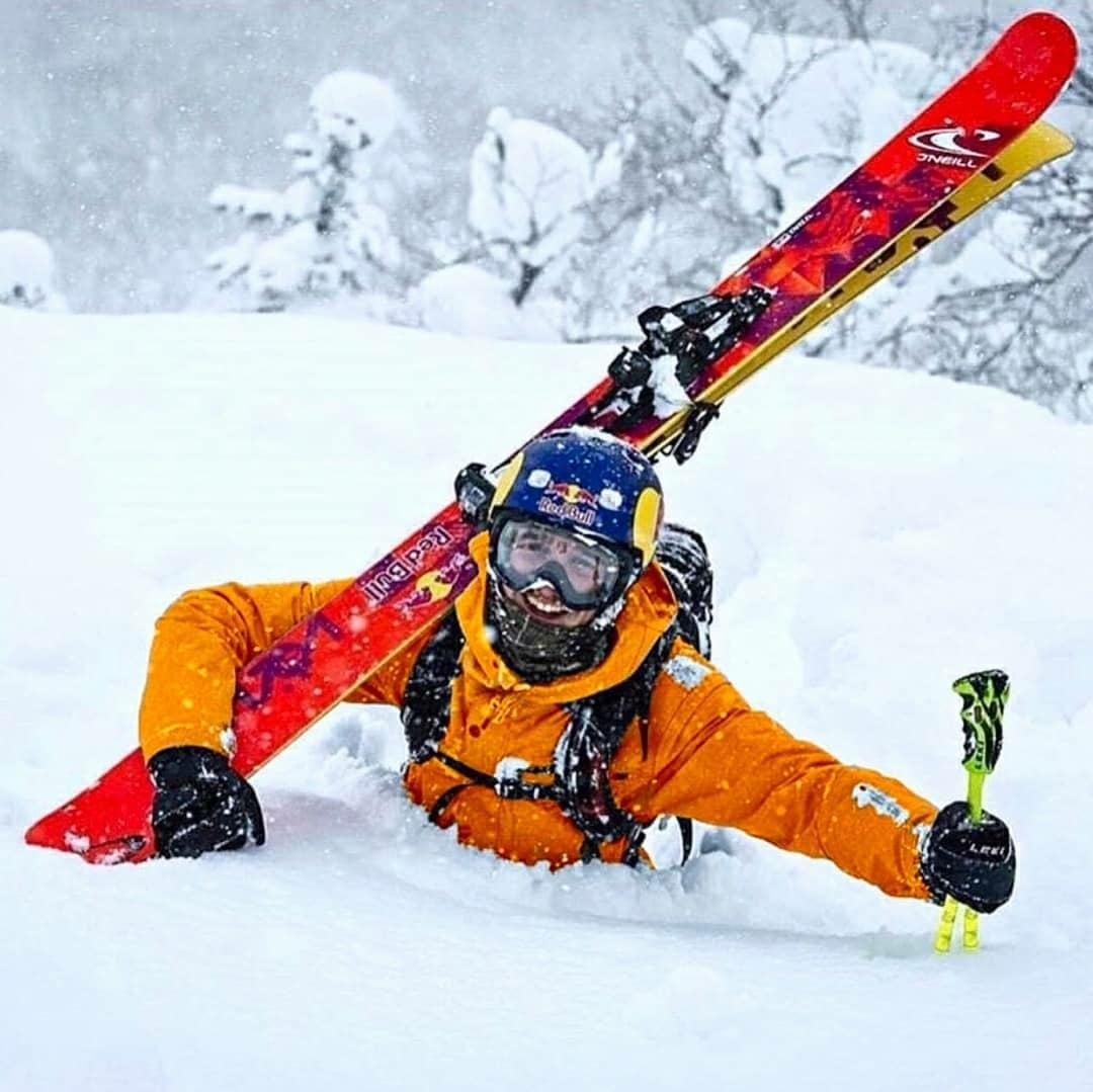 man walking through deep snow carrying skis