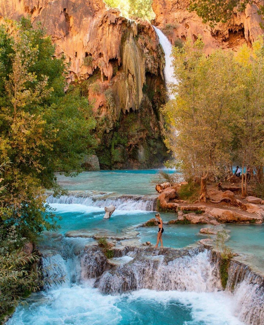 woman walking near waterfall