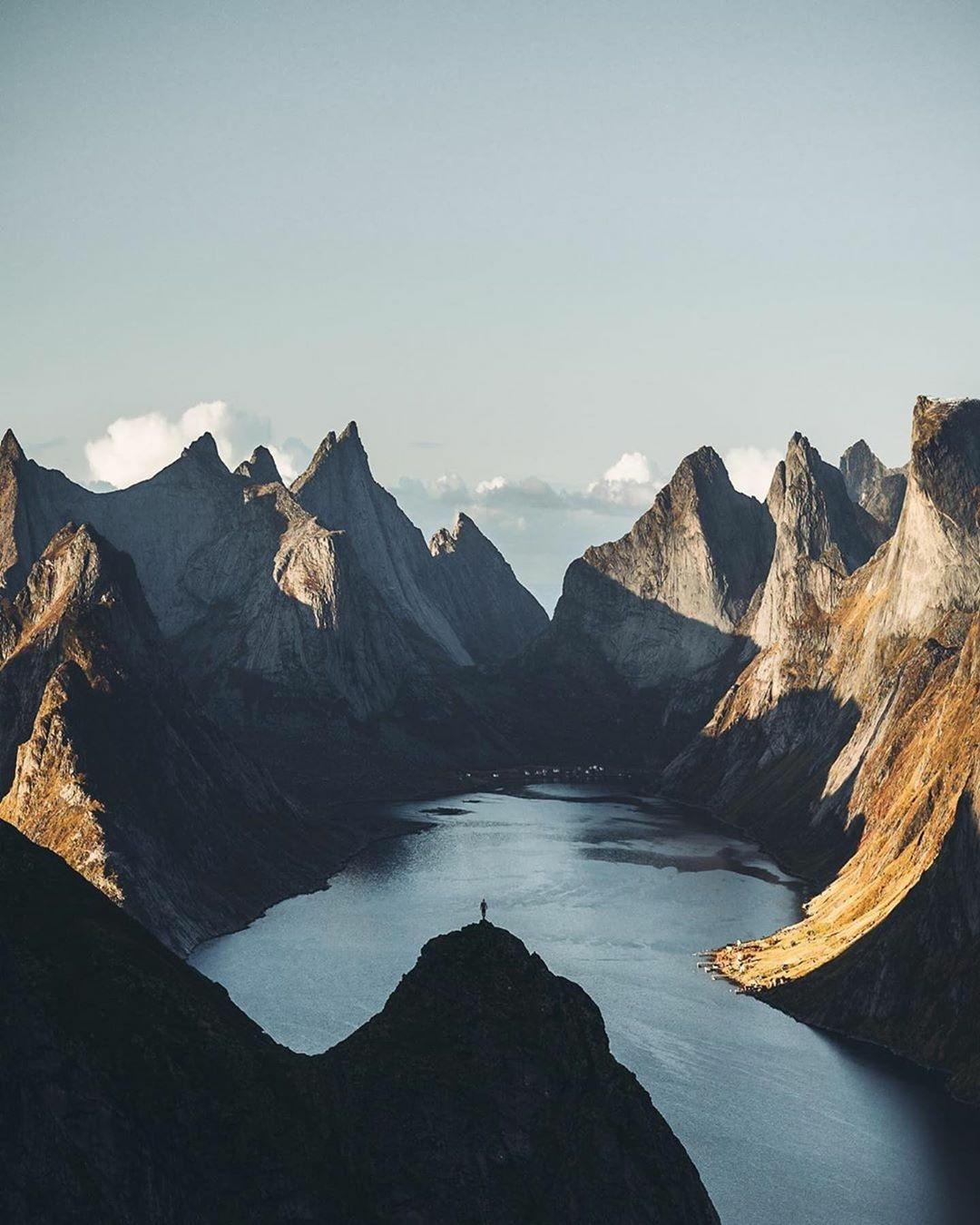man standing on ridge near mountain lake