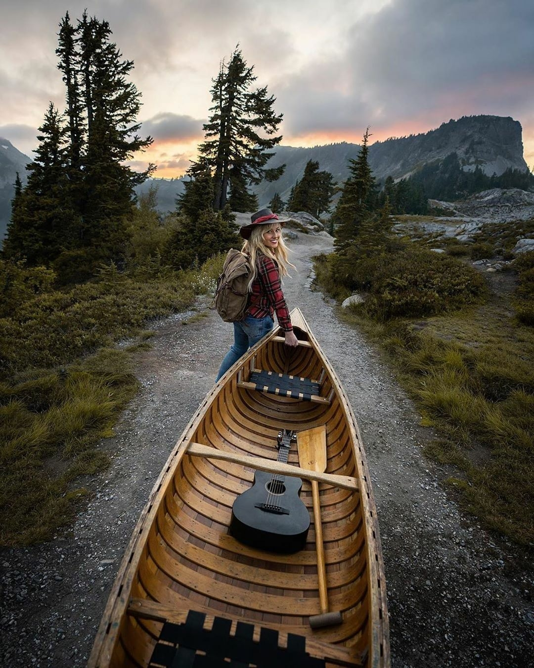 woman helping carry a canoe in the pacific northwest