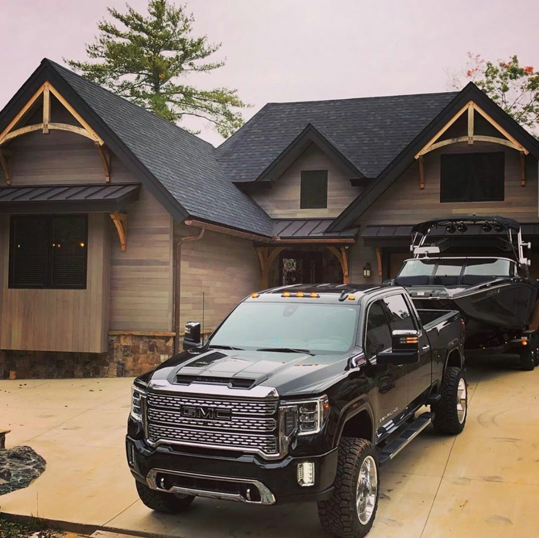 black gmc truck with black boat on driveway of home with black trim