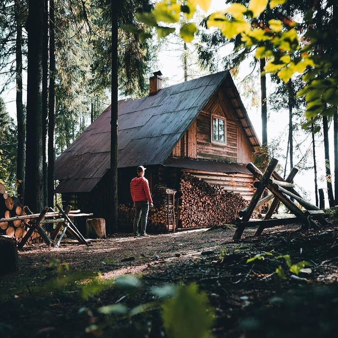 man standing in front of log cabin