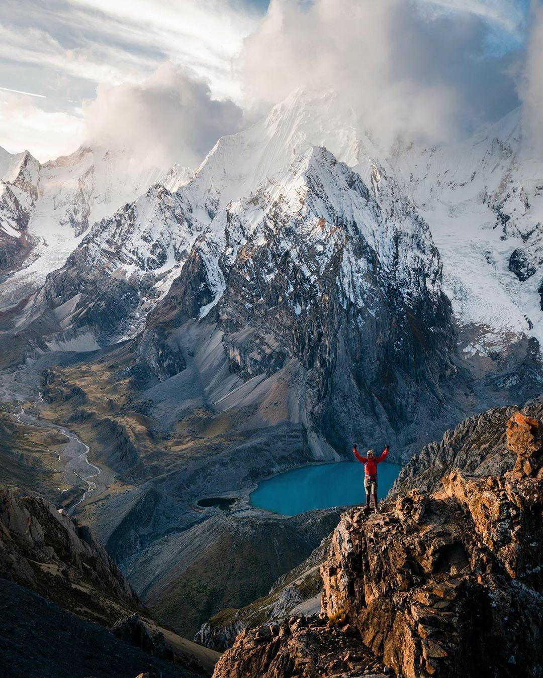 man standing on ridge of mountain