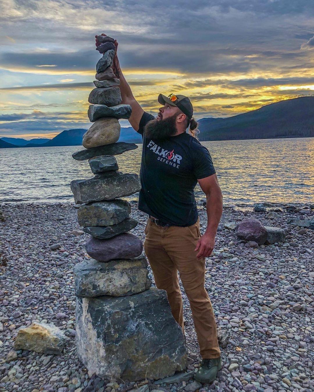 man stacking rocks near lake