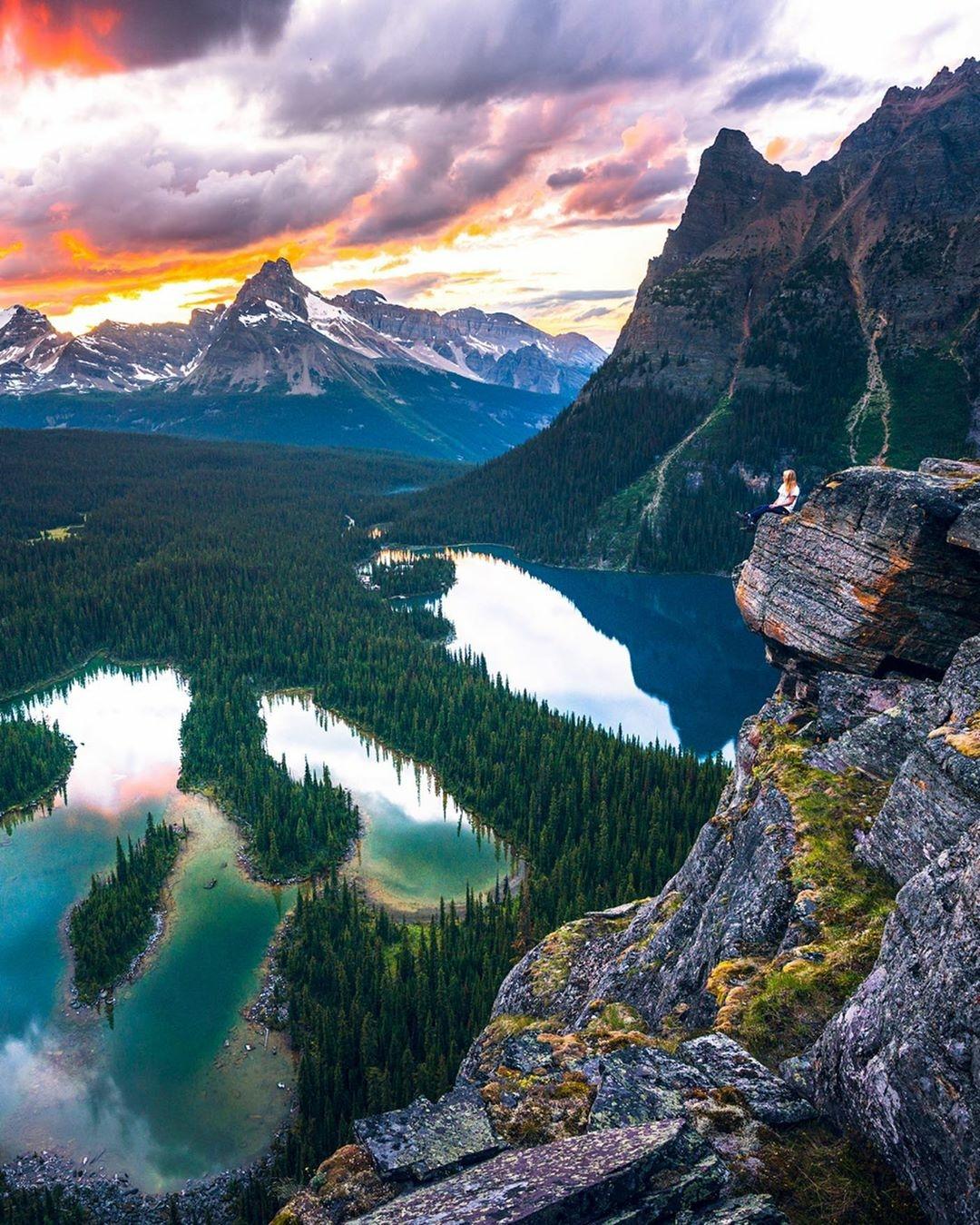 woman sitting on ridge over mountain lake