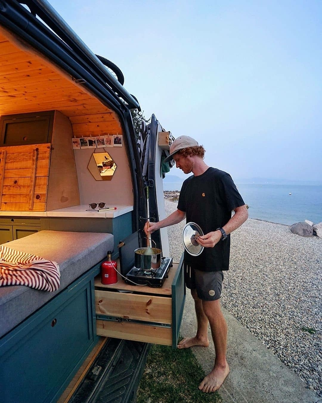 man cooking on camper van near ocean