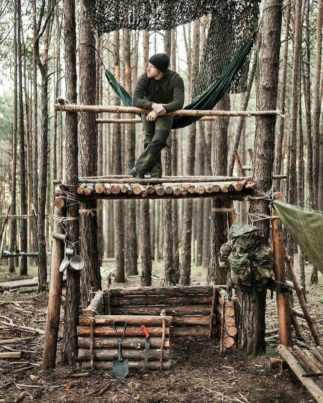 man standing on second deck of bushcraft shelter