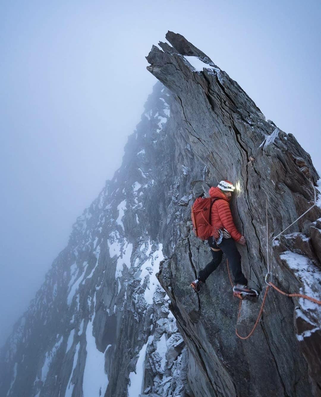 man climbing mountain top