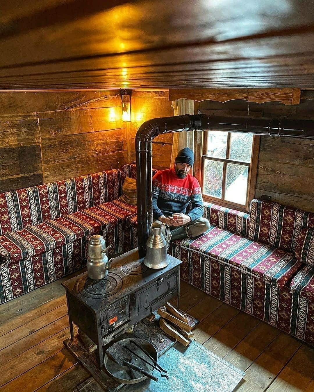 man sitting near cabin stove