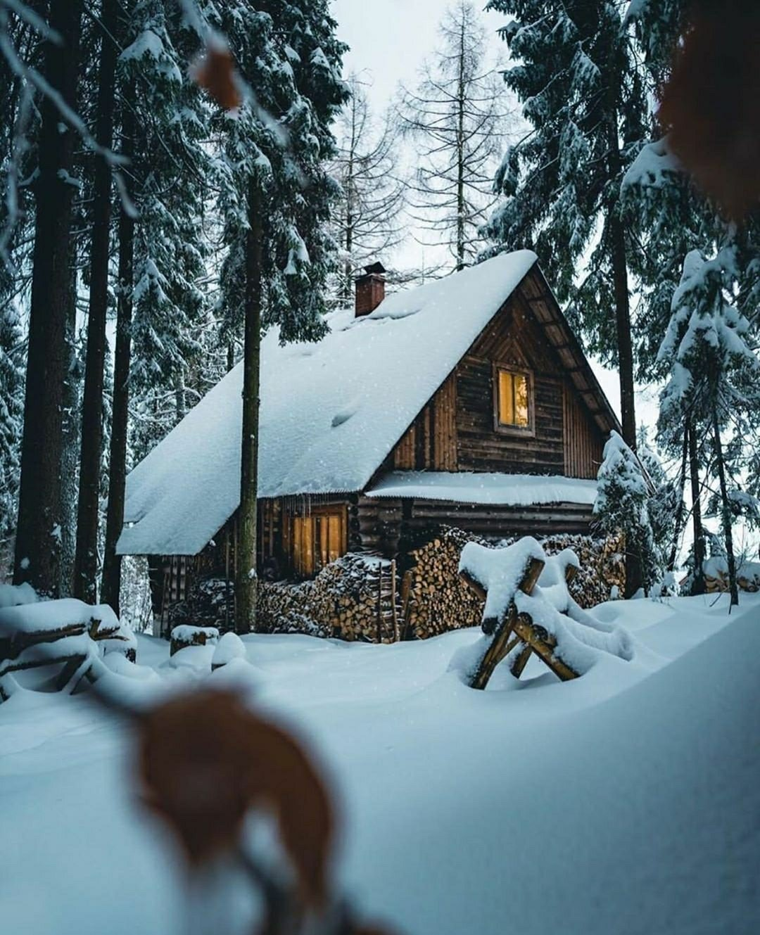 log cabin in snow with firewood