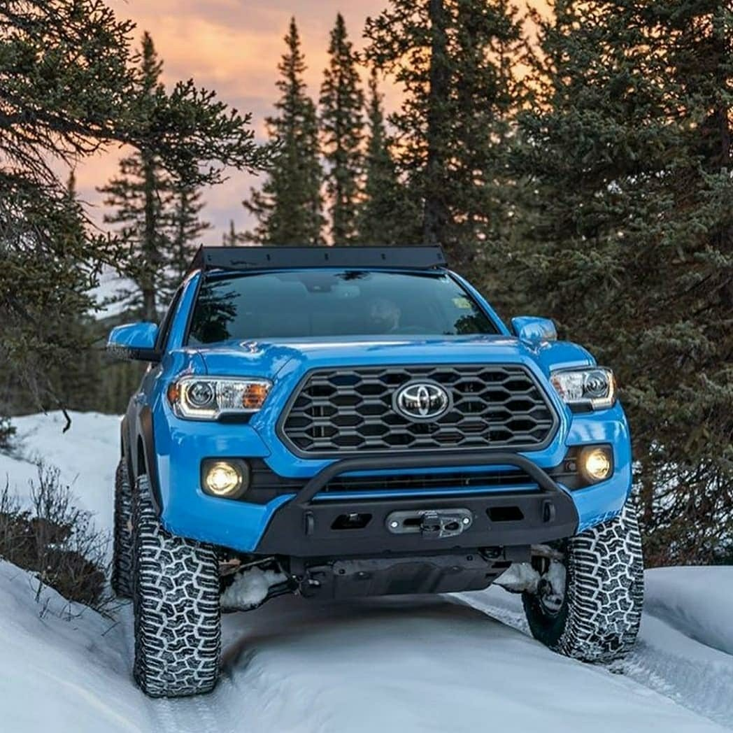 blue toyota tacoma exploring in the snow